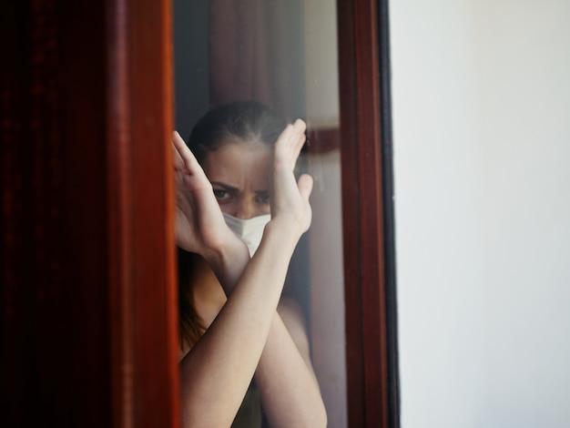 腕を組んで窓の外を見る女性