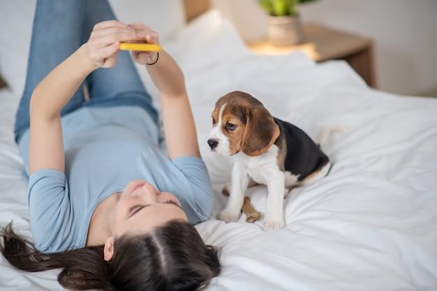 Женщина лежит на кровати и делает селфи