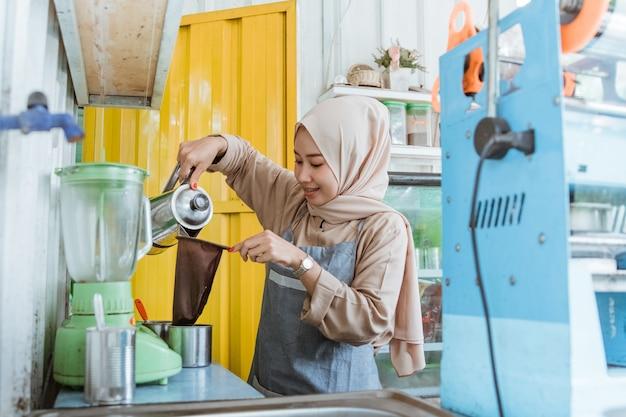 Женщина делает напиток из ситечка для чая в своем маленьком уличном продовольственном магазине