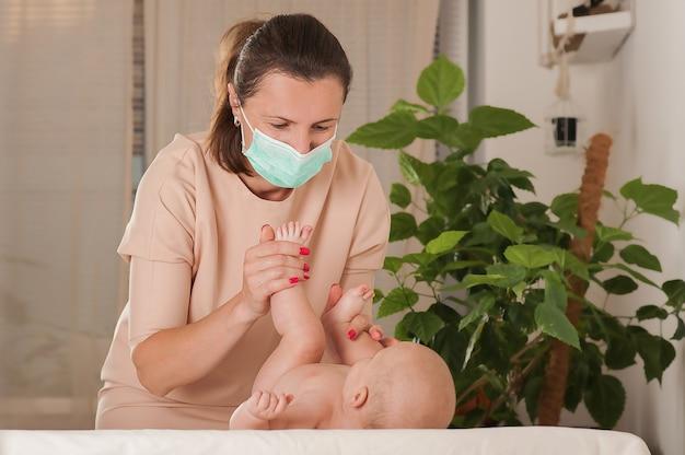 Женщина делает массаж новорожденному в медицинской маске.