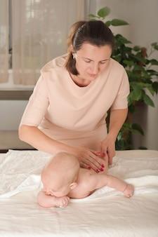 Женщина делает новорожденному массаж.
