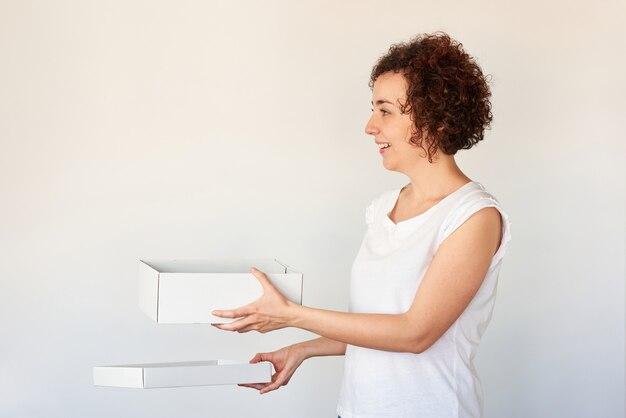 Женщина делает удивленное лицо, держа коробку