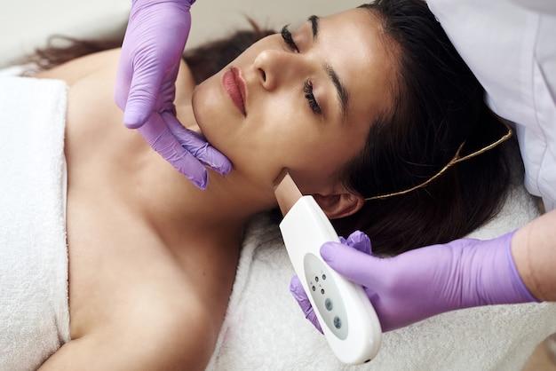한 여성이 고객에게 얼굴과 피부를 초음파 세척합니다. 현대 장비. 뷰티 살롱에서 치료를 받고 소파에 누워 젊은 예쁜 여자.