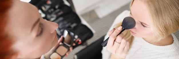 미용실의 한 여성 메이크업 아티스트가 브러시로 금발 여성의 피부에 파우더를 바르고 있다