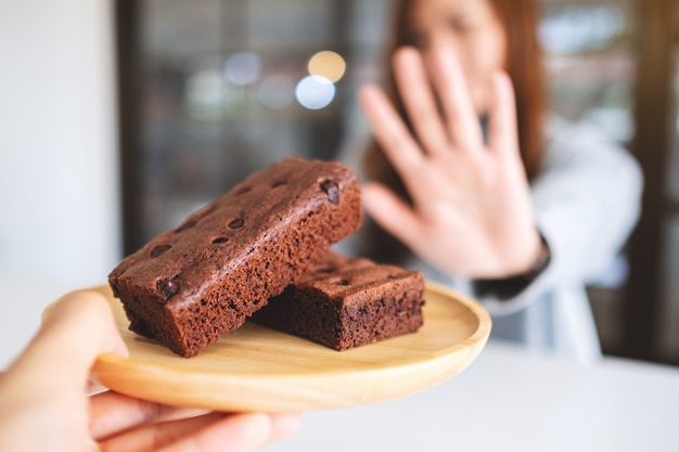 나무 접시에 브라우니 케이크를 거부하는 손 기호를 만드는 여자