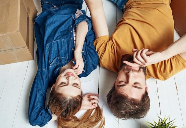 Женщина-мужчина с цветком в горшке лежит на полу в светлой комнате возле дивана.