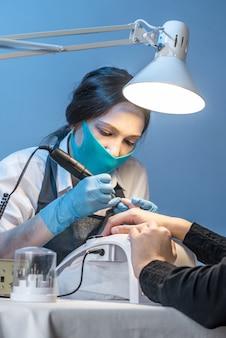 Мастер женского маникюра в салоне в процессе работы с ногтями клиента на синем фоне.