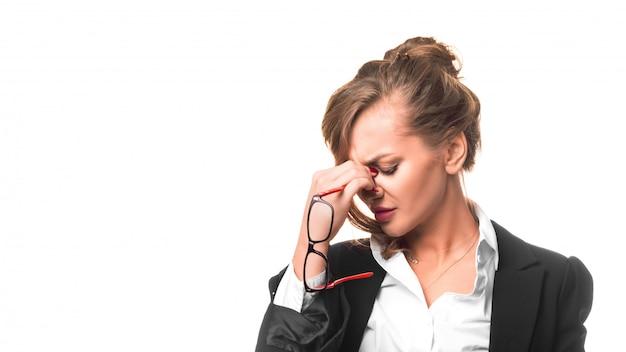 한 여성이 눈의 피로와 과로로 인해 코 다리를 마사지합니다. 심각한 비즈니스 우먼은 피곤합니다.