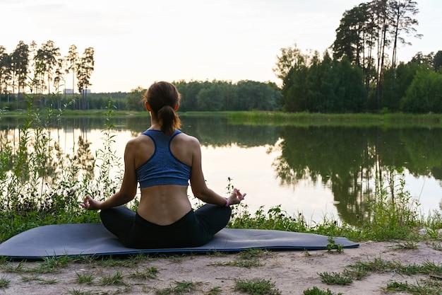 女性は湖のほとりで自然の中で瞑想します。人生の意味を実現するというコンセプト。夏の風景。