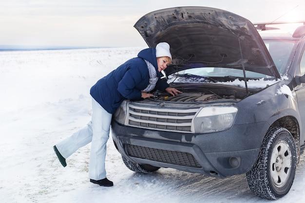 エンジンを修理しようとしている壊れた車の近くの女性。彼女は寒い。冬と雪原周辺。