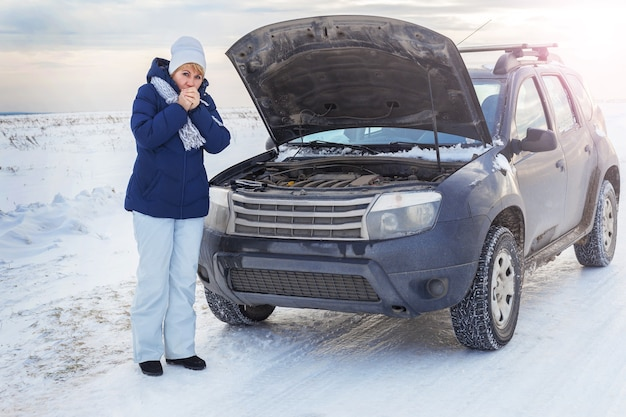 エンジンを修理しようとしている壊れた車の近くの女性。彼女は電話中です。彼女は寒い。冬と雪原周辺。
