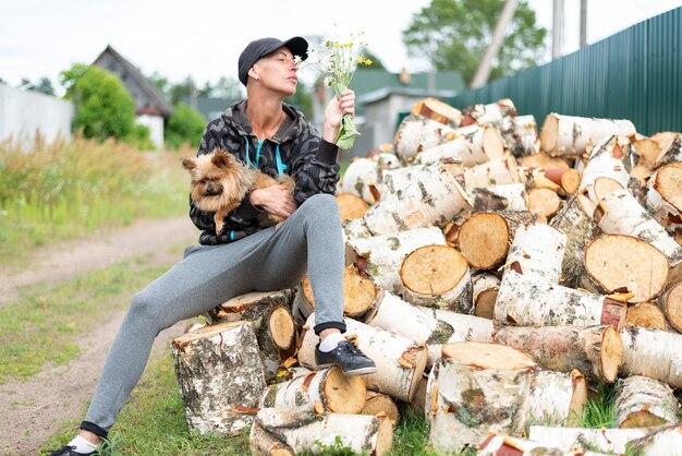 犬と一緒に、薪の山の近くの女性。あらゆる目的のために。