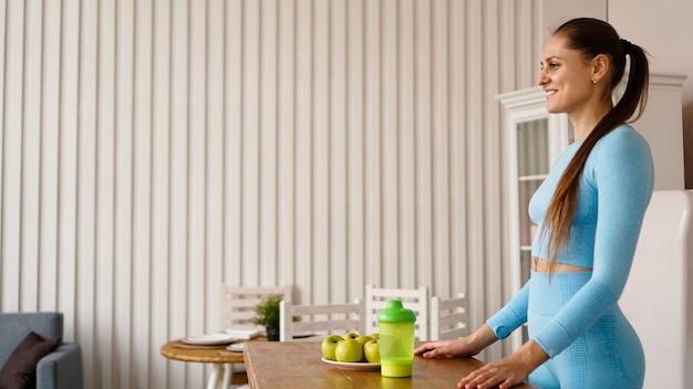 Женщина-диетолог рассказывает о пользе здорового питания на кухне. вид сбоку. концепция видеоблога или семинара о здоровом образе жизни