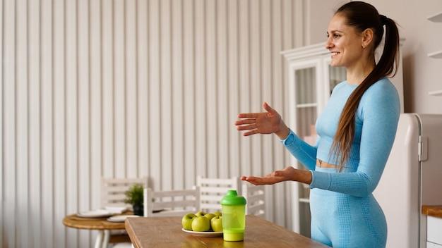 女性栄養士がキッチンでの健康的な食事の利点について話します。側面図。健康的なライフスタイルのビデオブログやセミナーのコンセプト