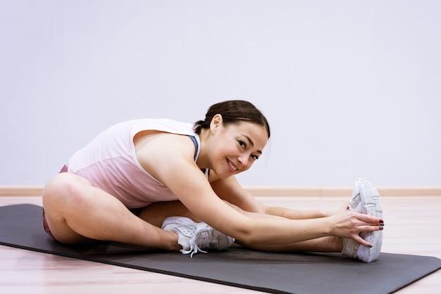 운동복을 입은 백인 여성이 집에서 벽을 배경으로 피트니스에 참여하고 있습니다. 건강한 라이프 스타일과 슬림 바디 컨셉