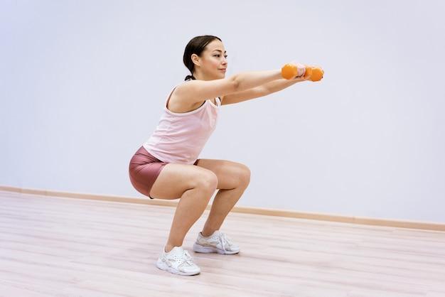 운동복을 입은 백인 여성은 가벼운 벽을 배경으로 손에 아령을 들고 쪼그리고 앉습니다. 홈 스포츠 개념