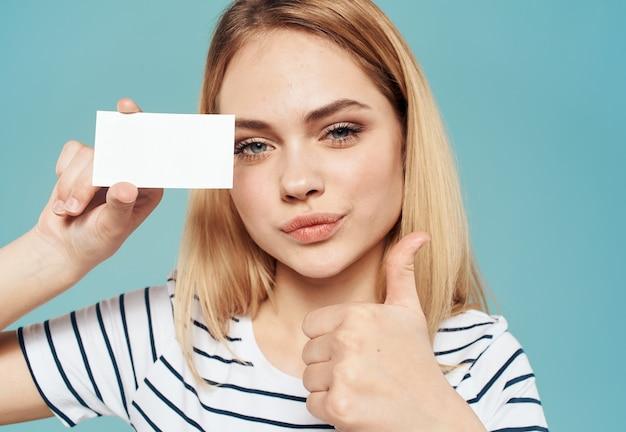 Женщина на синем в полосатой футболке с визиткой в руке