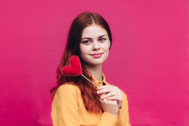 ピンクの背景の女性は彼女の手に布で作られた赤いハートを持っていますバレンタインデー