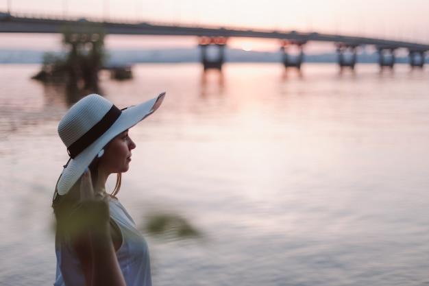Женщина на берегу реки на закате профиль портрет кавказской женщины в соломенной шляпе расслабляющий и ...