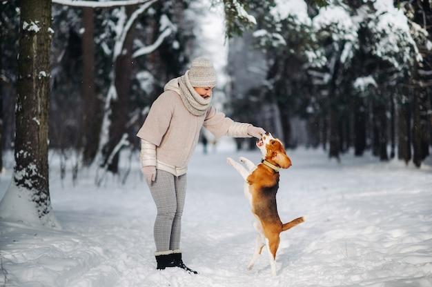 冬の森で犬と散歩中の女性。雪に覆われた森での愛人と犬のゲーム。