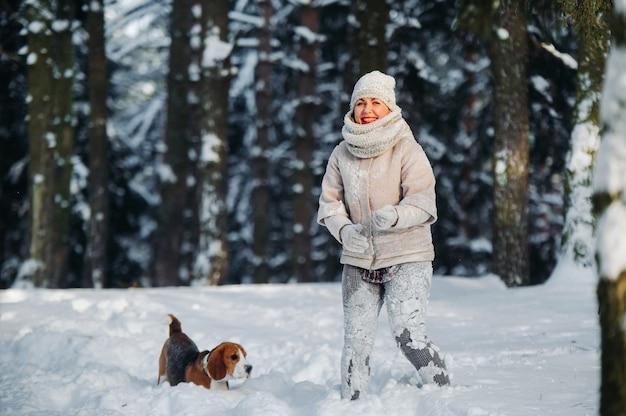 겨울 숲에서 그녀의 강아지와 함께 산책에 여자. 눈 덮인 숲에서 여주인과 개 게임.