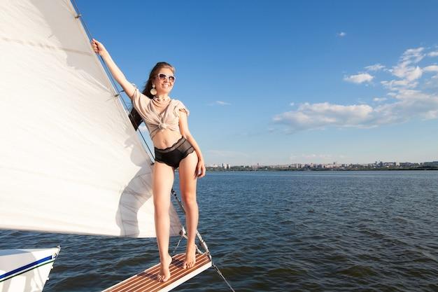 コピースペースと白い帆のスペースに対するヨットの女性。海とヨットで夏休みのコンセプトです。