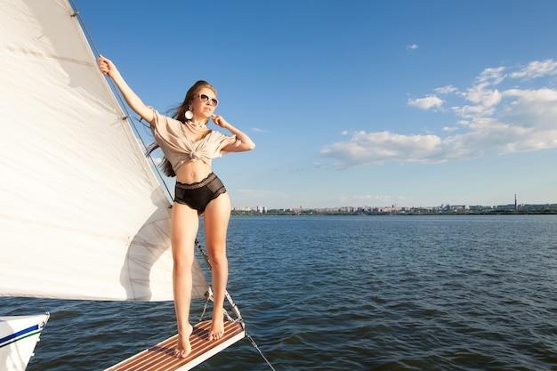 白い帆と空を背景にヨットに乗った女性ボートトリップのコンセプト