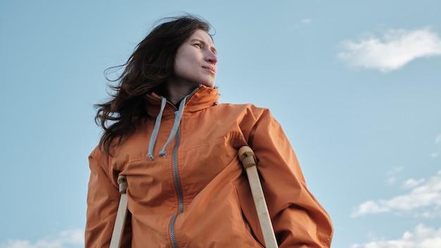 松葉杖をつけた女性が湖のほとりを歩いています。穏やかな湖と地平線上の雲を背景に砂浜