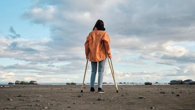 목발을 짚은 여성이 호숫가를 따라 걷고 있습니다.