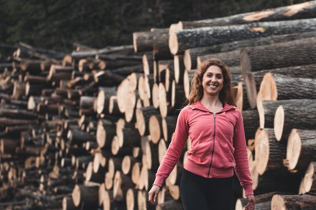 トラックスーツの丸太を背景にした女性が森の中を歩きます。