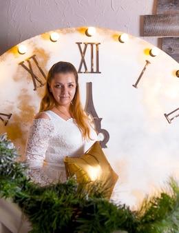 새해 시계의 배경에 있는 여자. 축제 크리스마스 분위기