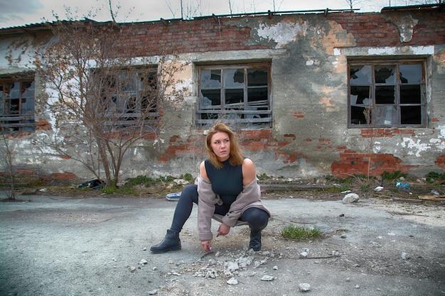 Женщина на развалинах в разрушенном городе с мусором.