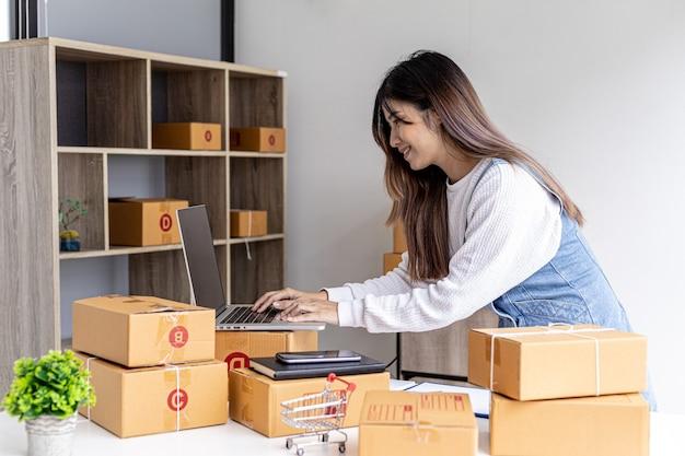 オンラインストアのオーナーが、ウェブサイトから注文した顧客に入力して話しかけ、オンラインで販売し、ラップトップにメッセージを入力し、梱包用の小包ボックスを入力しています。オンライン販売のコンセプト。