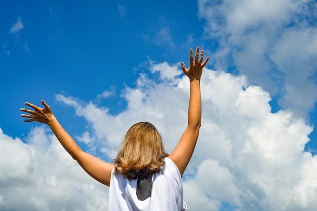 女性または少女が立って、手を空に伸ばします。少女は青い空に向かって手を上げた