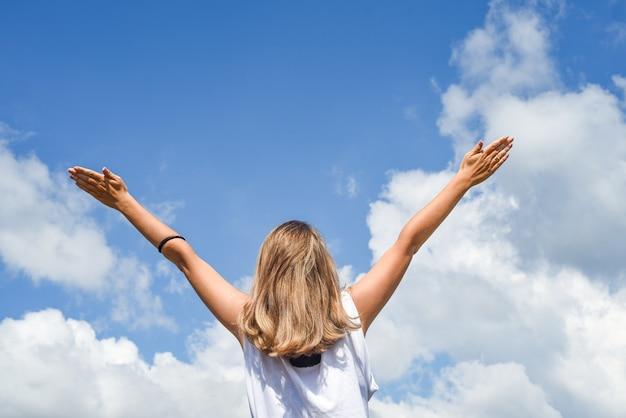 Женщина или девушка стоит спиной и протягивает руки к небу. девушка подняла руки к голубому небу