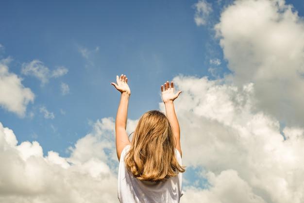 Женщина или девушка стоит спиной к камере и протягивает руки к небу.