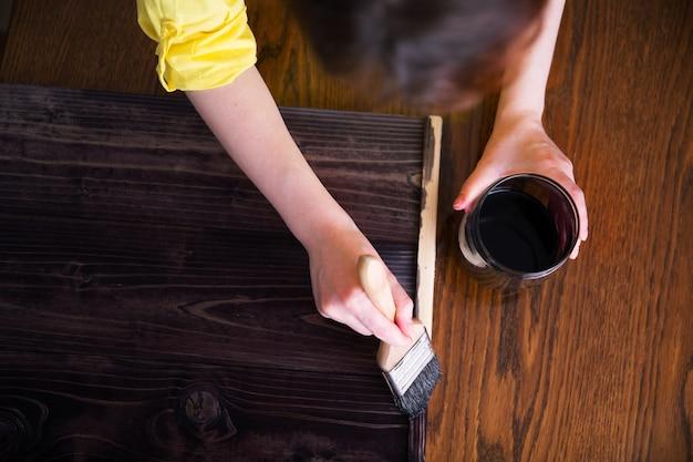 女性は黒檀の木の染みで板を塗ります。