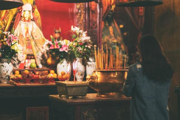 중국 사원에서 불상에 경의를 표하는 여성