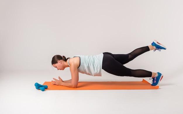 女性が白で足を上げてマットの上で運動をする