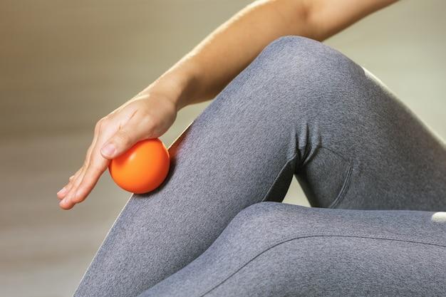 여자는 마사지 볼로 다리 근육의 근막 이완을 수행합니다.