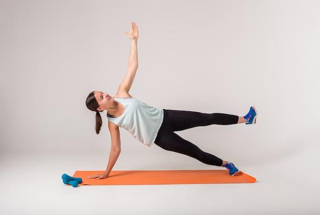 女性が運動側板を実行し、白を見上げる