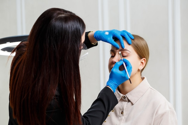 Женщина-мастер перманентного макияжа рисует эскиз бровей на лице своей клиентки.