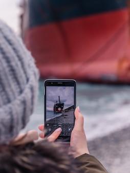浜辺を歩きながら、岸に係留された大型船を携帯電話で撮影する女性