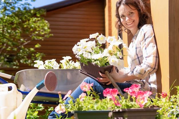 庭に植物や花を植える女性。彼女は家の前の階段に座っています。