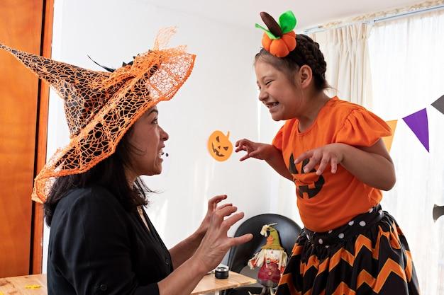ハロウィーンを装った女の子、カボチャの衣装を着た女の子、魔女の衣装を着た女性の両方で遊んでいる女性