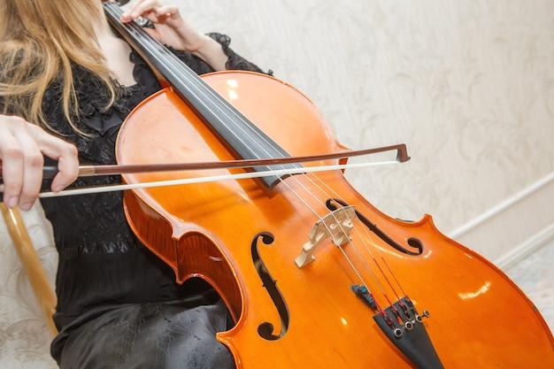 女性は明るい背景で茶色のバイオリンを弾きます