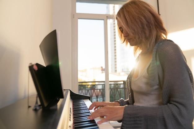 밝은 햇빛이 창문을 통과하는 큰 창문을 배경으로 한 여성이 전자 피아노를 연주합니다.