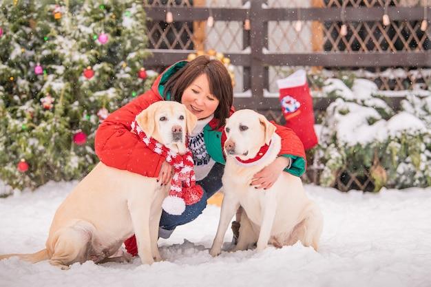 アパートの建物の中庭で冬の降雪時に飾られたクリスマスツリーの近くで女性がlabradorsmi犬と遊ぶ。