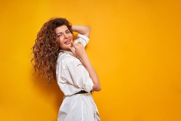 女性がポーズをとる。巻き毛の若い幸せな女性は人生を楽しんでいます。感情的に微笑む、笑う。彼女は白いシャツを着ています。