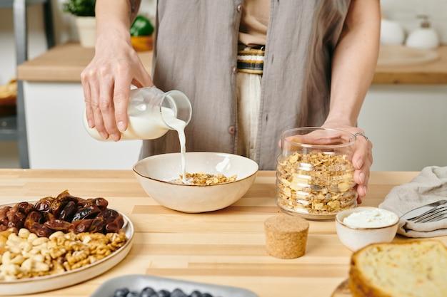 식탁 옆 콘플레이크가 든 그릇에 우유를 붓는 여성